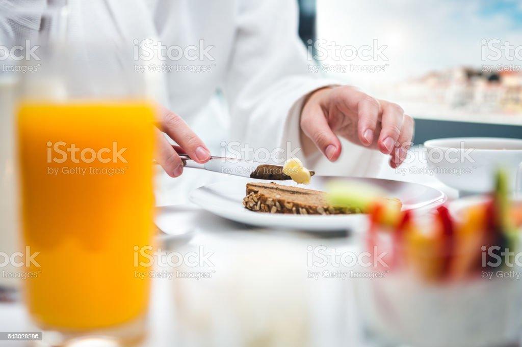 Woman Having Breakfast In Hotel Room stock photo