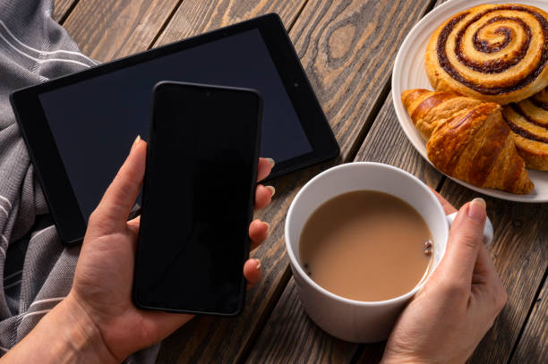 A woman having breakfast on a rustic table checking the latest on her electronic devices while having tea and pastry. Holding a smartphone on her left hand and a cup on the right. stock photo