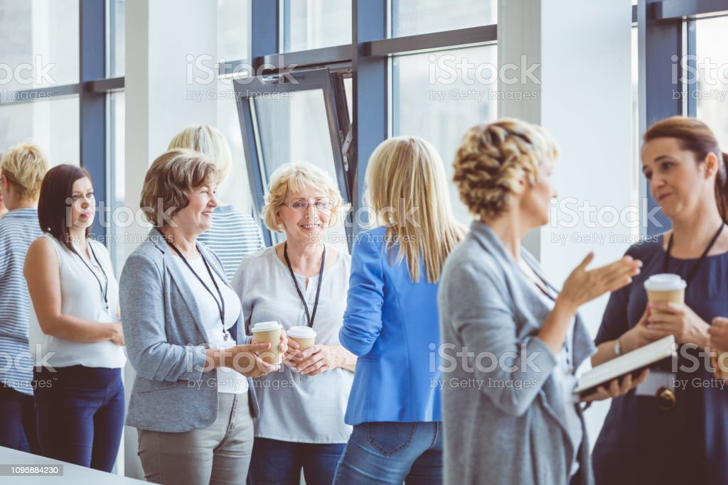 Woman having casual discussion during break in seminar Break during a women seminar in convention center. Women standing in seminar hall having coffee and talking. Adult Stock Photo