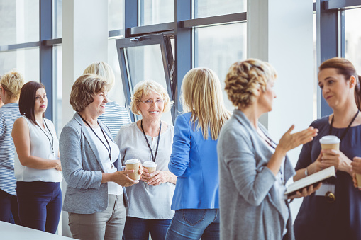 Woman Having Casual Discussion During Break In Seminar Stock Photo - Download Image Now
