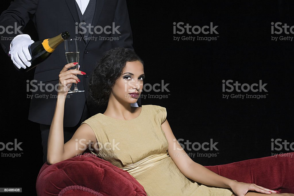 Woman having champagne served by servant stock photo