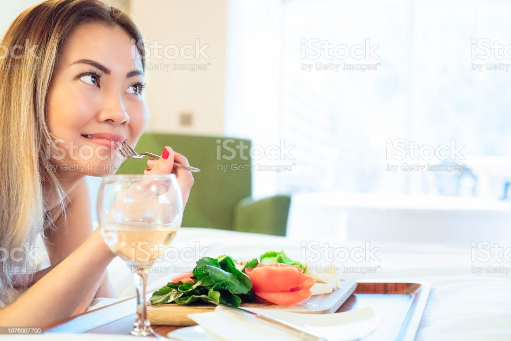 Asian woman having cheese board with white wine in bed and smiling -...