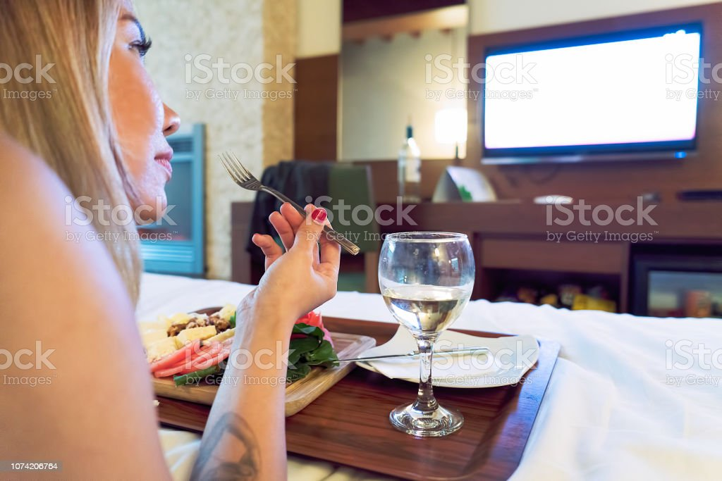 Asian Woman having cheese board with wine in bed watching tv, holding...