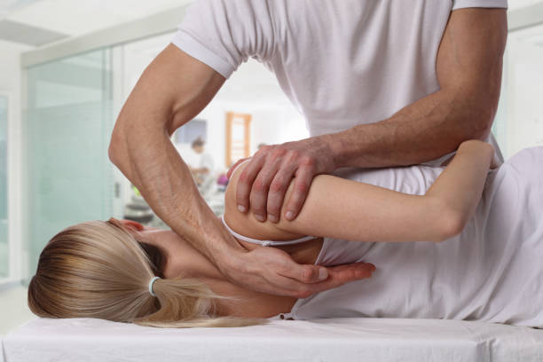 woman having chiropractic back adjustment. osteopathy, alternative medicine, pain relief concept. physiotherapy, sport injury rehabilitation - chiropractic care stock photos and pictures