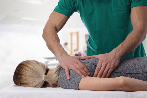 woman having chiropractic back adjustment. osteopathy, alternative medicine, pain relief concept. physiotherapy, sport injury rehabilitation - medicina sportiva foto e immagini stock