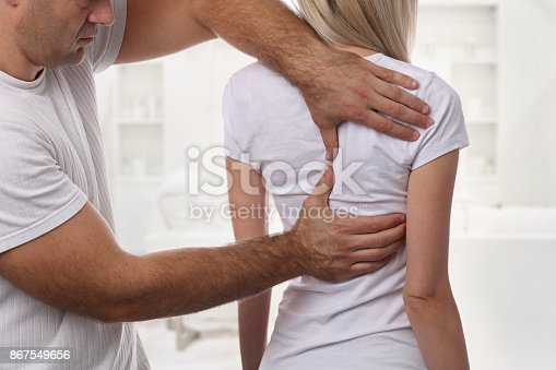 863158416istockphoto Woman having chiropractic back adjustment. Osteopathy, Physiotherapy, sport injury rehabilitation concept 867549656