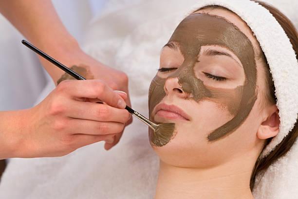 Mujer con máscara de cara de Chocolate aplicada por esteticista del Spa - foto de stock