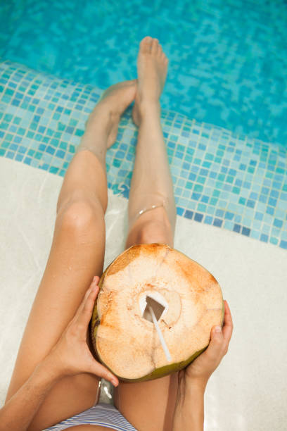 woman having coconut at the beach - woman leg beach pov stock photos and pictures