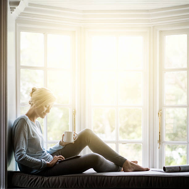 woman having coffee while using digital tablet on window sill - brightly lit stock photos and pictures
