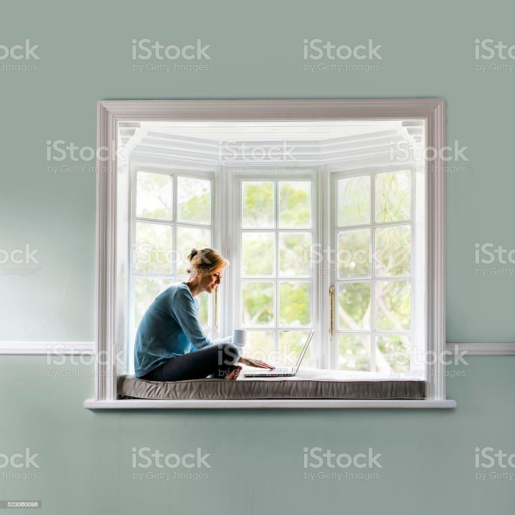 Frau mit Kaffee und benutzt Laptop auf Fensterbank – Foto