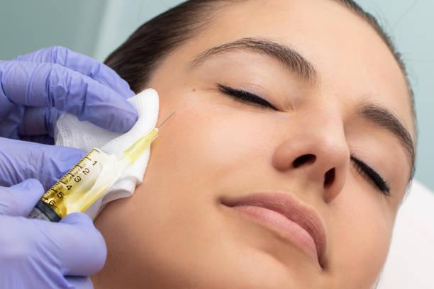 Woman having cosmetic hormone facial treatment. stock photo