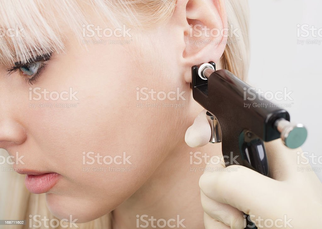 Woman having ears pierced with ear piercing gun stock photo
