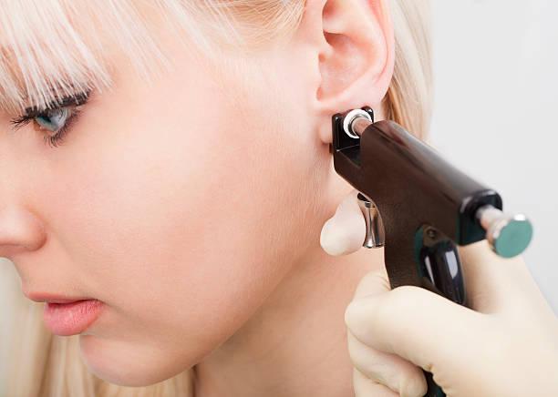 frau, ohren piercing mit ohr-piercing gun - ohrringe stock-fotos und bilder