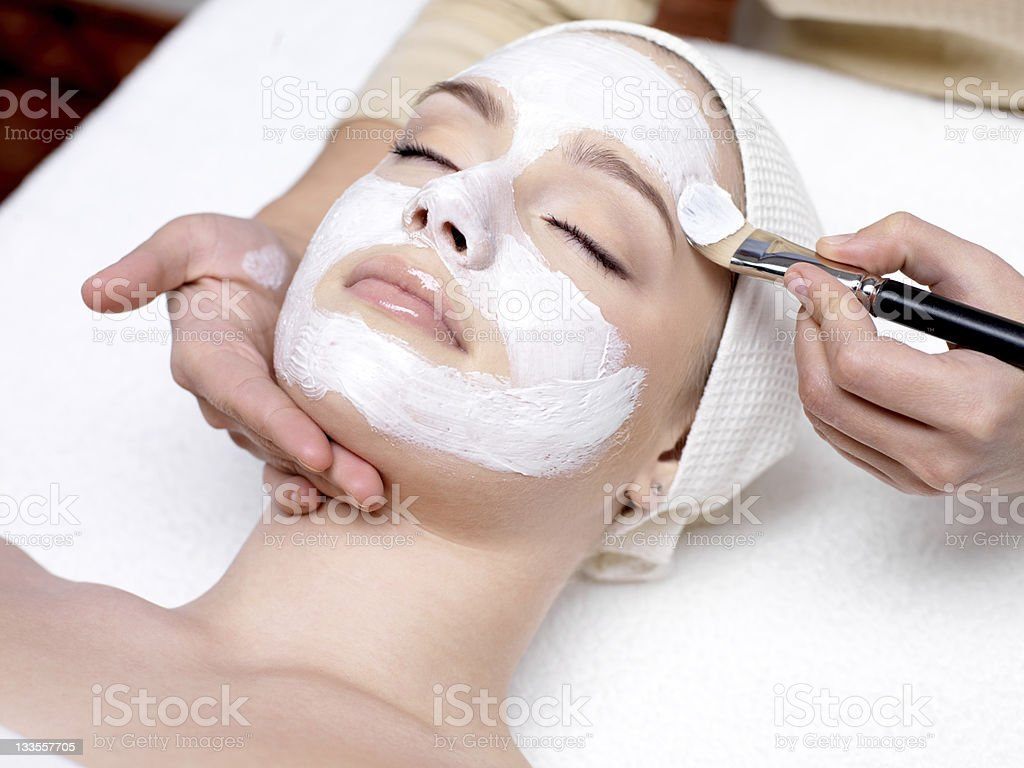 Woman having facial mask at beauty salon stock photo