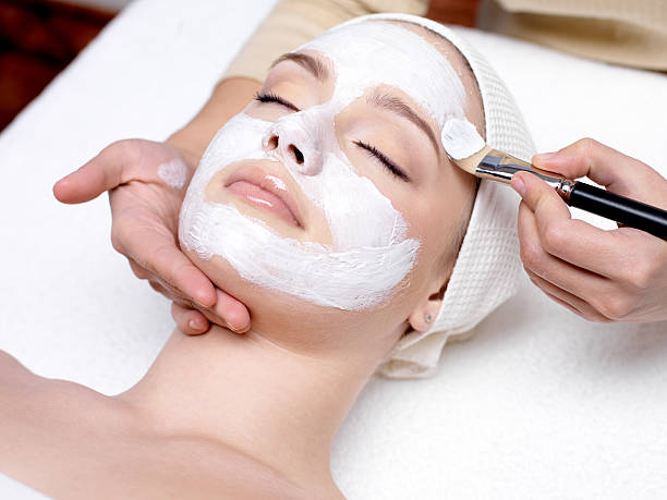 woman having facial mask at beauty salon - beauty treatment stock photos and pictures
