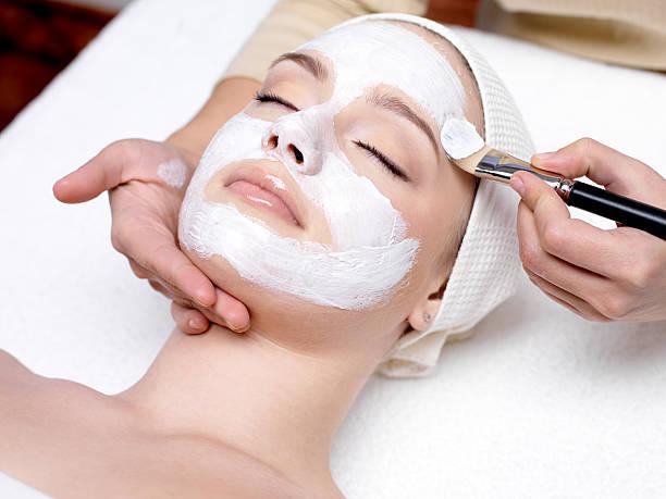woman having facial mask at beauty salon - 美容治療 個照片及圖片檔