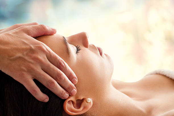 woman having facial massage. - holistic medicine stock photos and pictures