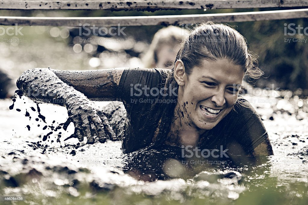 woman having fun crawling in mud stock photo