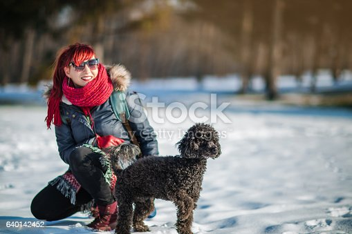 istock Woman having fun in winter park with their dog 640142452