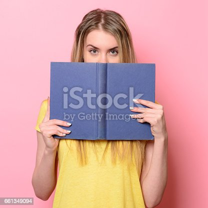 istock Woman having fun on study process and reading a book 661349094
