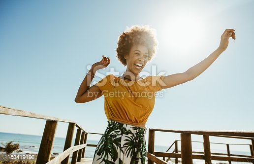 Excited young woman running on a boardwalk with her hands raised on a sunny day. African female having fun on summer vacation at the seaside.