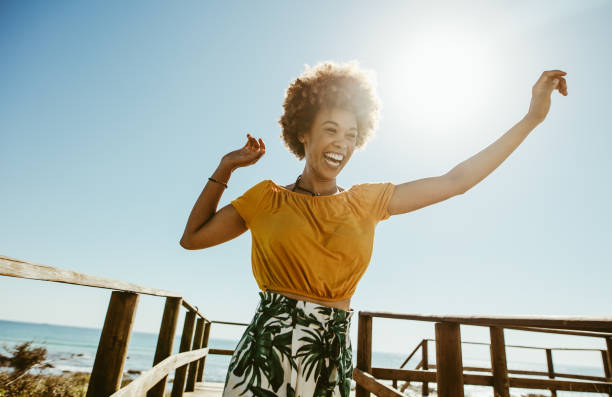 Woman having fun on summer vacation Excited young woman running on a boardwalk with her hands raised on a sunny day. African female having fun on summer vacation at the seaside. lifestyles stock pictures, royalty-free photos & images