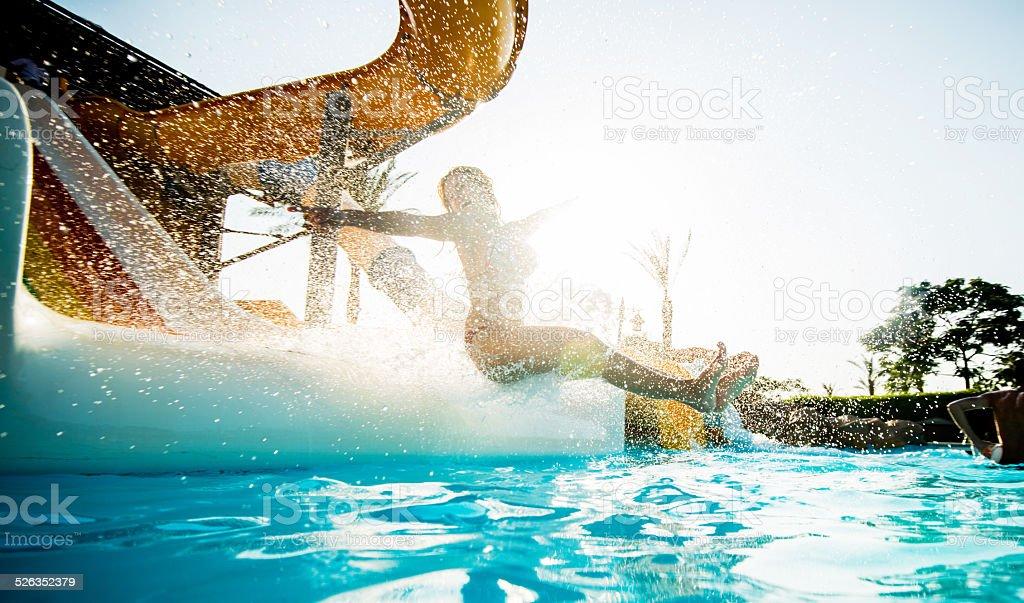 Woman having fun on water slide. stock photo