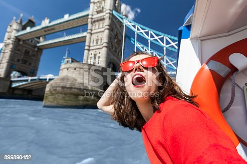 Young woman having fun on boat in front of Tower bridge in London