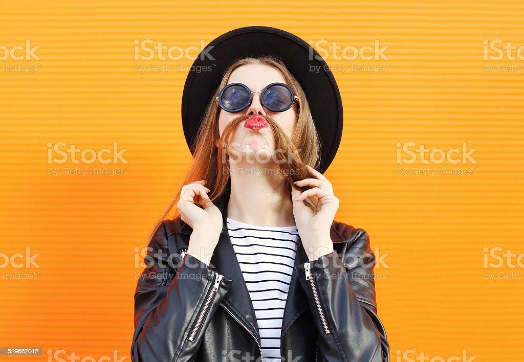 Woman having fun shows moustache hair over orange background stock photo