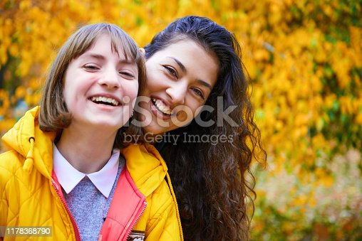 istock woman having fun with autumn leaves in city park, outdoor portrait 1178368790