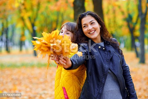 istock woman having fun with autumn leaves in city park, outdoor portrait 1179001493