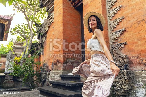 Cheerful young female is walking while travelling to asia and visiting local temple. Website banner