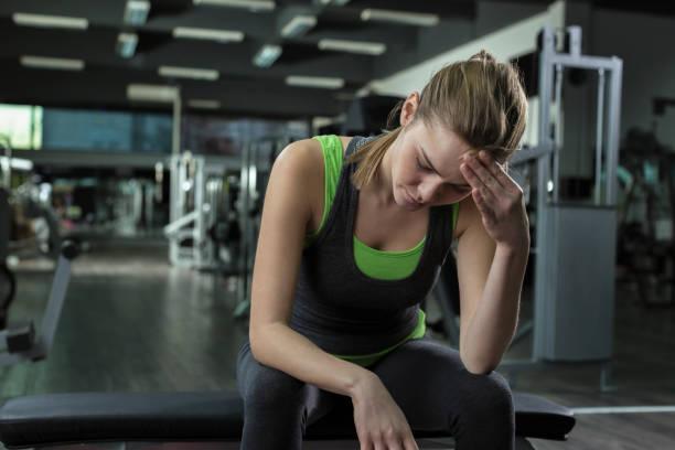 vrouw met hoofdpijn na het trainen in een healthclub - atlete stockfoto's en -beelden