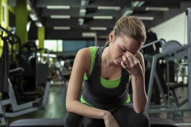 Frau, die Kopfschmerzen nach einem Training im Fitnessstudio – Foto