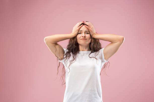 frau, die kopfschmerzen. rosa hintergrund isoliert. - frustration stock-fotos und bilder