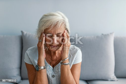 Woman having headache migraine. Stress and depression. Health care, pain, stress, age and people concept - face of senior woman suffering from headache