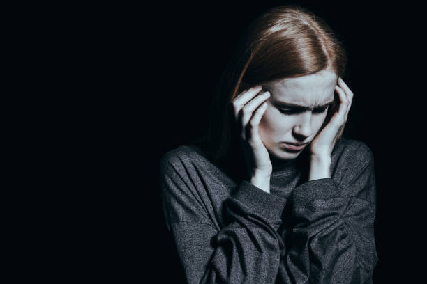 Woman having headache Young woman with depression and anxiety having bad headache post traumatic stress disorder stock pictures, royalty-free photos & images