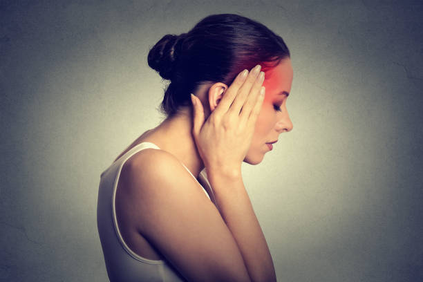 Woman having headache with her head in her hands isolated on gray wall background stock photo