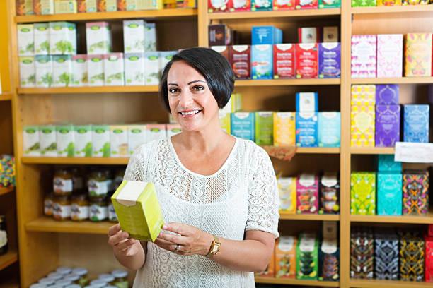 woman having health supplements in box in drugstore - teeladen stock-fotos und bilder