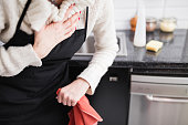 istock Woman having heart / chest pain and problems during house work in the kitchen. 1198388560