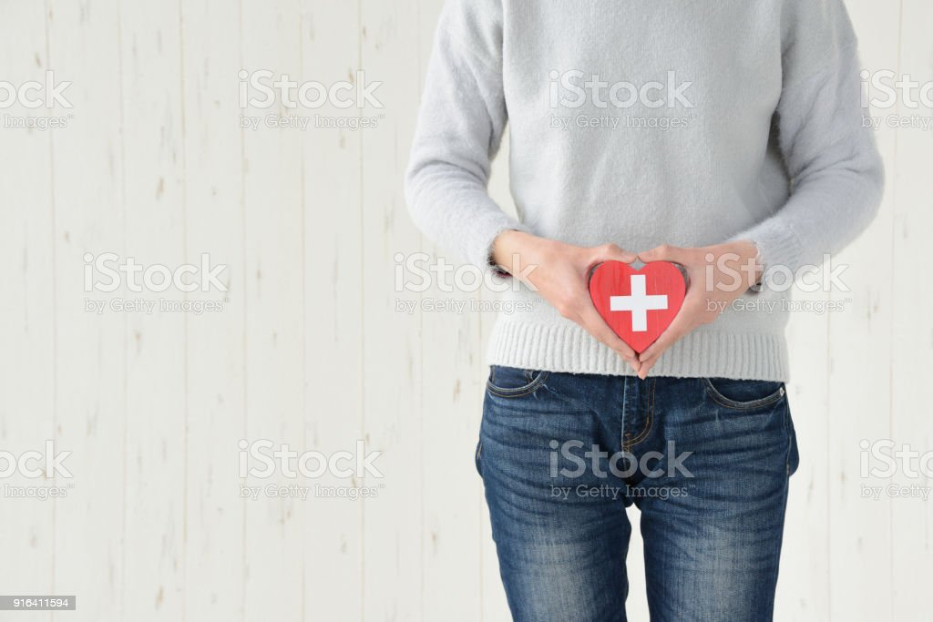 Woman having heart object on lower abdomen stock photo