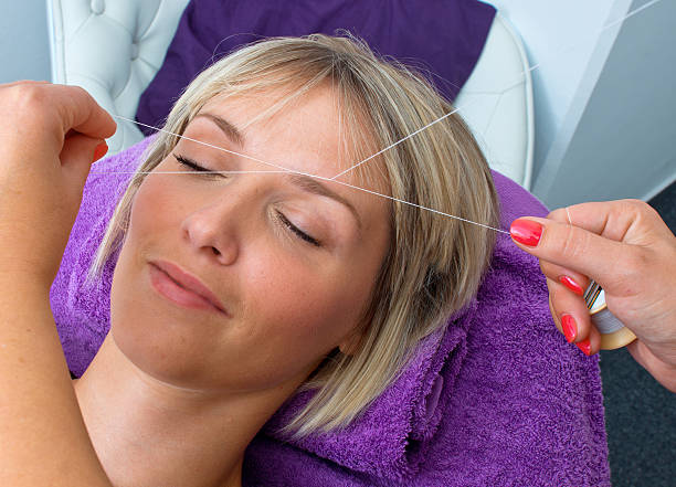 Woman having her eyebrows threaded attractive blond woman having threading hair removal procedure threading stock pictures, royalty-free photos & images