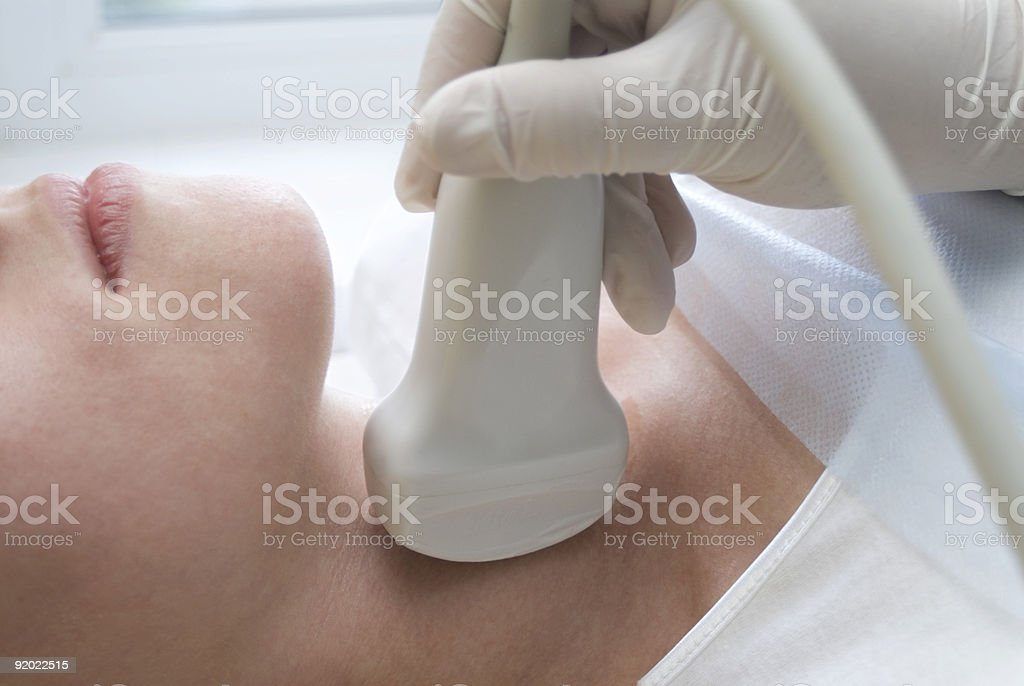 Woman having her neck scanned with ultrasound stock photo