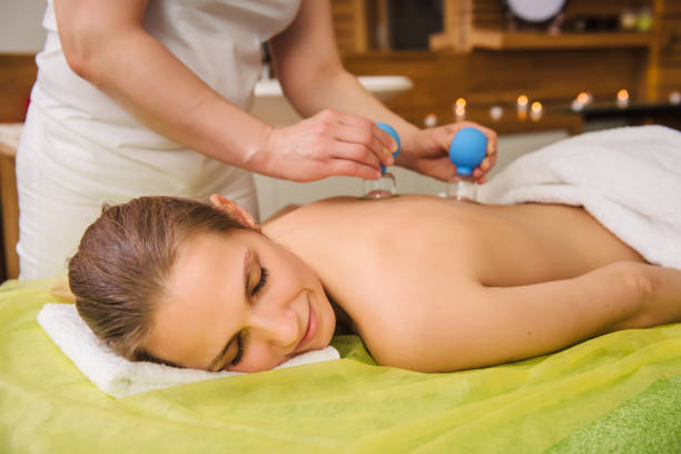 Woman having hot jar vacuum cupping massage in spa center stock photo