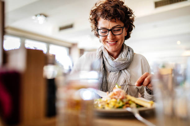 Woman having lunch at a restaurant Photo of woman having lunch at a restaurant one mature woman only stock pictures, royalty-free photos & images