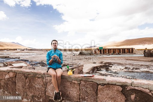 Happy woman having dinner near hot spring after exploring the geyser valley in the mountains of Atacama region, Chile