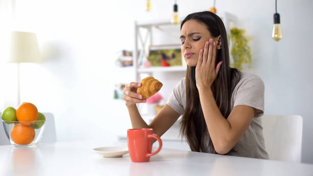 Woman having lunch, eating croissant with coffee, feeling toothache from sweets stock photo