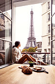 Woman having breakfast in hotel in Paris. The image is a composition.
