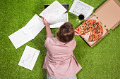 Woman having lunch with pizza and glass of wine working  on the grass using laptop with graphics and charts printed on the paper.