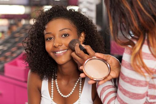 Woman having makeup applied.